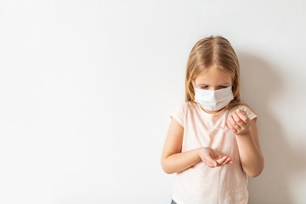 きれいな手に手の消毒剤アルコールゲルを使用して小さな女の子