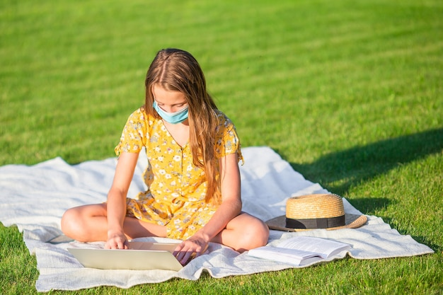 Little girl using laptop to study outdoors in the park