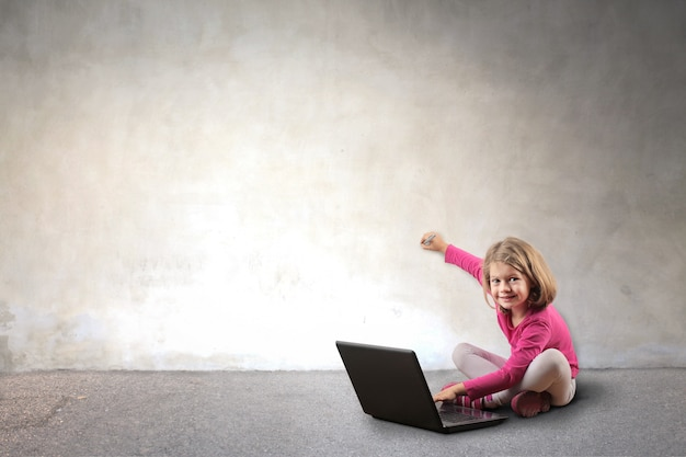 Little girl using a laptop and writing on a wall