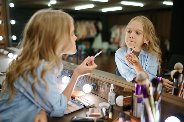 메이크업 살롱에서 거울에 립스틱을 사용하는 어린 소녀