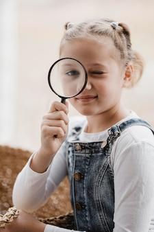 Little girl using a magnifier