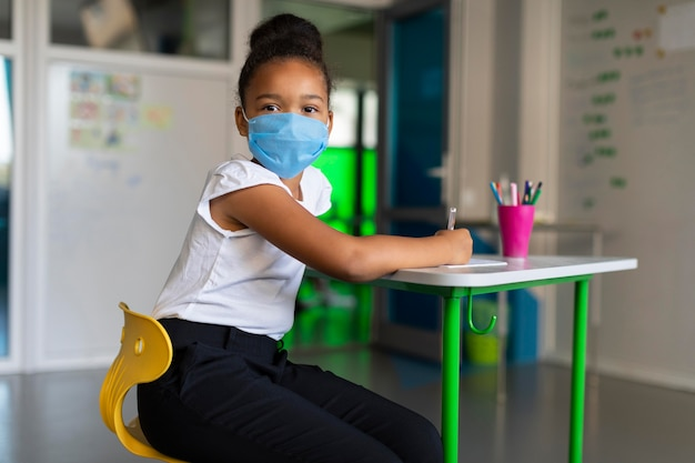 Little girl using a medical mask in class