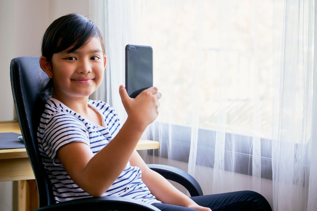 ビデオ通話にスマートフォンを使用している小さな女の子