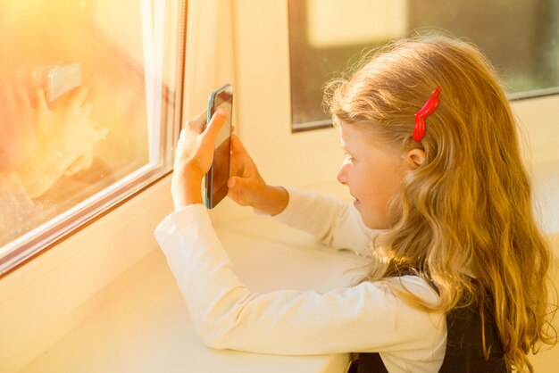 Little girl using wi-fi on mobile phone
