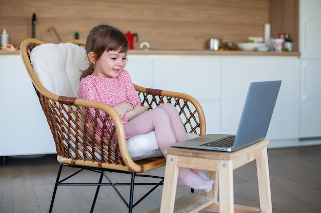 Маленькая девочка разговаривает по видео с бабушкой и дедушкой, используя ноутбук