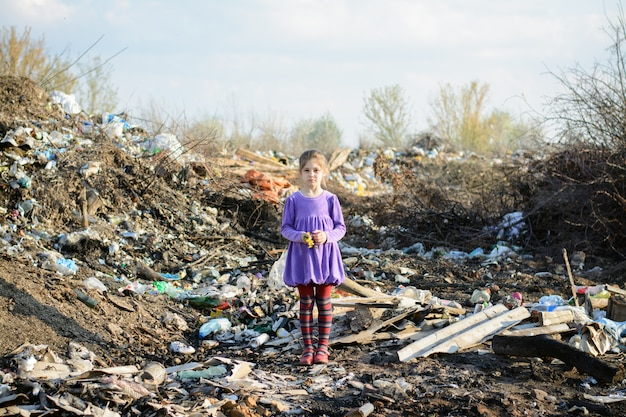 Little girl in a violet dress and red striped tights strands in a city dump among piles of garbage holding yellow faded flowers