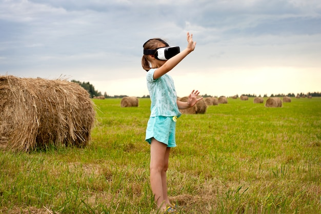 A little girl in virtual reality glasses, standing in the field and playing.