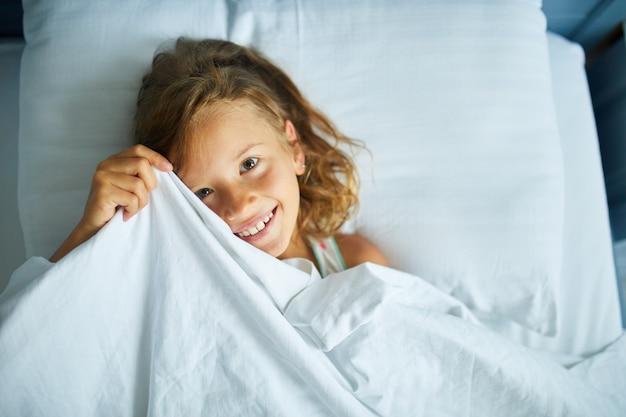 어린 소녀는 집에서 크고 아늑한 흰색 린넨 침대에서 잠에서 깨어납니다