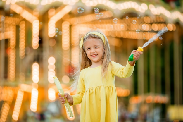 Little girl on a walk in an amusement park with soap bubbles