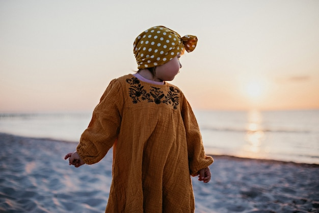 Little girl walking along the beach and turning to the water and the sun