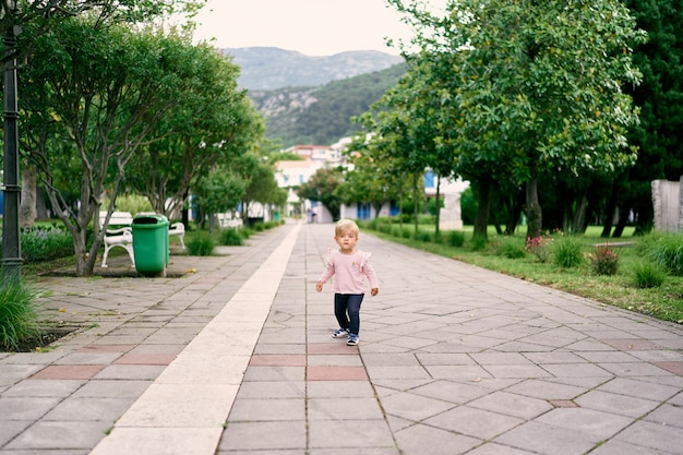 Little girl walking along the paved road in the park against the background of green trees and