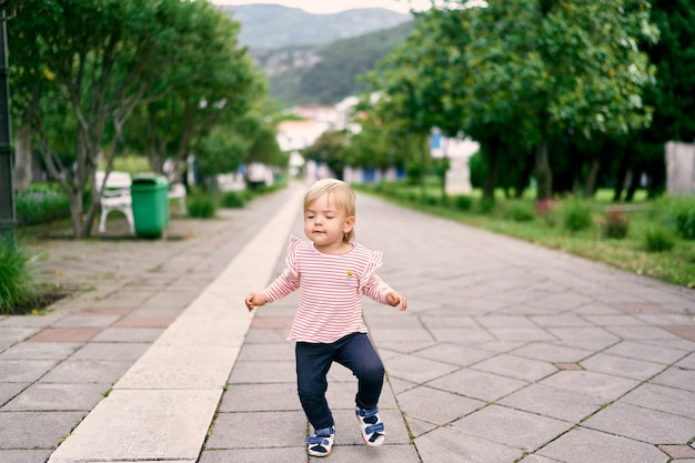 Little girl walking along the road in the park against the background of green trees