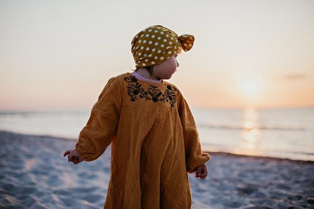 ビーチを歩いて水と太陽に目を向ける少女