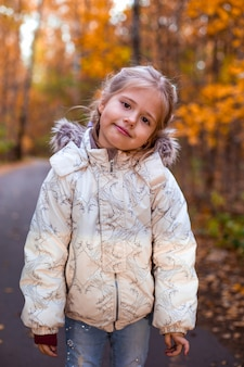 Little girl walking in autumn forest in white clothes in road