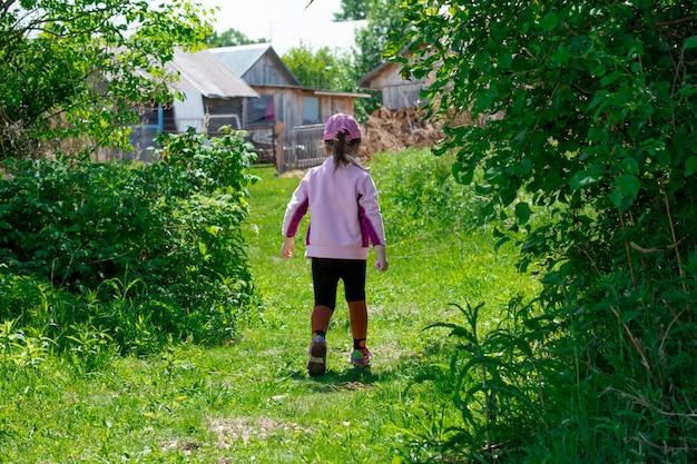 Маленькая девочка гуляет во дворе летом