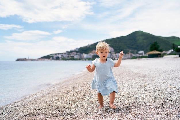 손에 자갈을 들고 자갈 해변을 걷는 어린 소녀