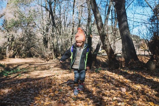 Маленькая девочка, идущая по листву