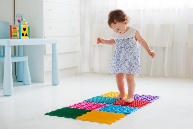 Маленькая девочка, ходить на массажный коврик