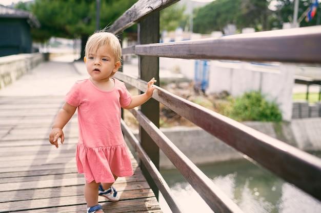 강 다리 위를 걷는 어린 소녀