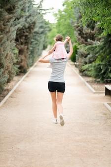 公園の母親の肩の上を歩く少女
