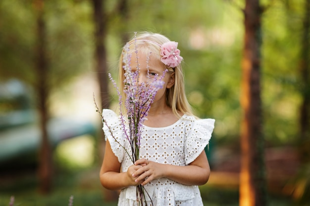 Little girl walking in park. adorable girl sniffing flowers in summer.