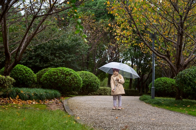 Little girl walking in a park under an umbrella during a rain