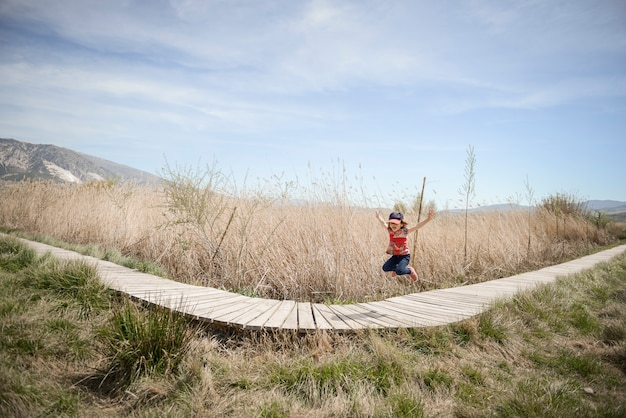 Little girl walking on a path of wooden boards in a wetland in padul, granada, andalusia, spain