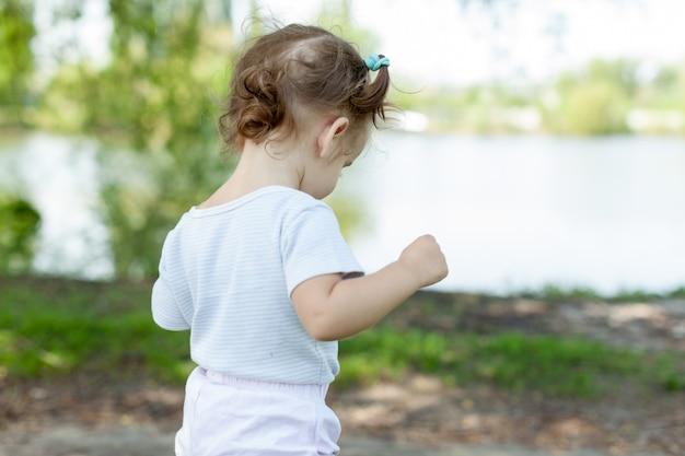Little girl walking and playing outside near lake