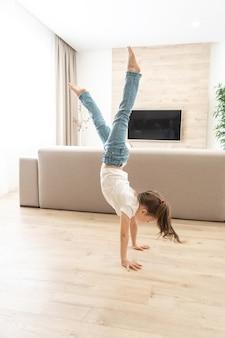 Маленькая девочка идет вверх ногами на руках у себя дома