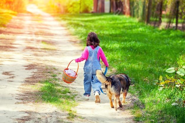 Маленькая девочка гуляет с собакой по дороге обратно к камере