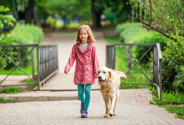 Маленькая девочка гуляет с золотистым ретривером на открытом воздухе в парке