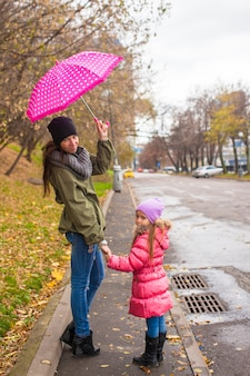 Little girl walking with her mother under an umbrella on a rainy day