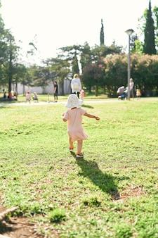 어린 소녀는 공원의 푸른 잔디를 따라 멀리 걷는 사람들에게 걸어갑니다.