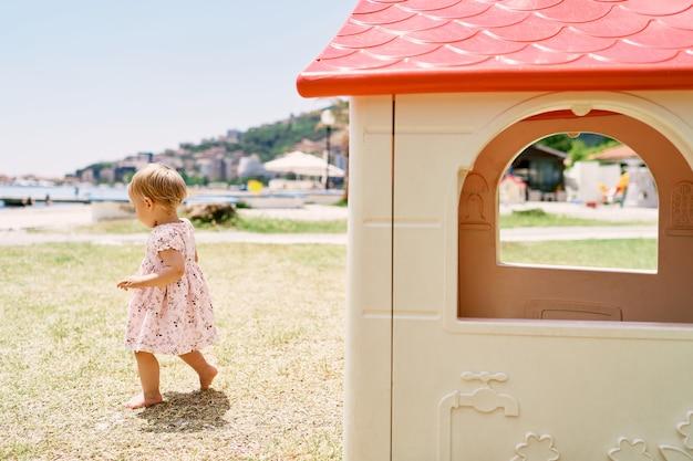 小さな女の子はおもちゃの家を背景に遊び場に沿って歩きます