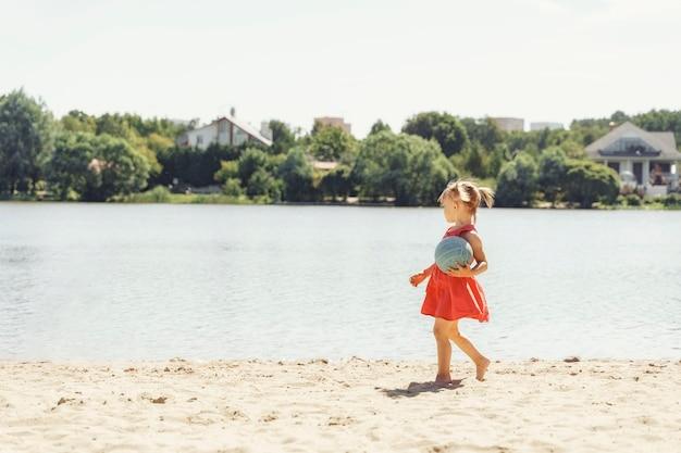 어린 소녀는 공을 강둑을 따라 산책. 여름 휴가 개념. 텍스트 및 복사 공간을위한 공간