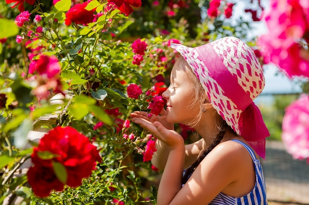 小さな女の子はバラの咲く庭で歩きます。ピンクのリボンと帽子をかぶって立ち、テキスト用のスペース