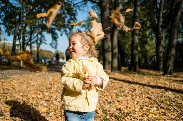 Маленькая девочка гуляет в парке осенью и бросает листья.