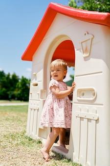 小さな女の子が遊び場のおもちゃの家に入る