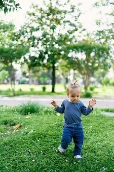小さな女の子は、木の背景に野花と緑の芝生の上を歩きます