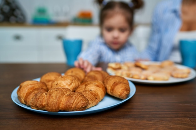 Little girl wants to take croissant in the kitchen