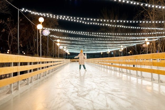 Little girl in warm clothing learning to skate on the rink in winter evening in the park