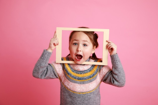 Little girl in warm dress looking through frame on rosa bachground.