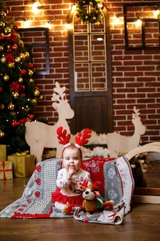 A little girl in warm sweater sits under a christmas tree with toys and gifts with horns on her head. happy childhood. new year holiday atmosphere