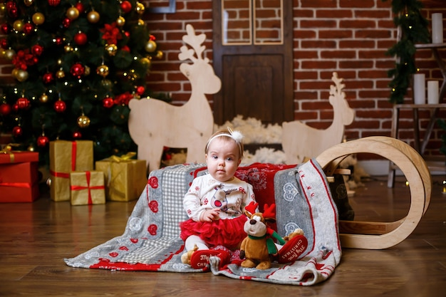 A little girl in a warm sweater stands with a christmas tree with toys and gifts. happy childhood new year festive atmosphere
