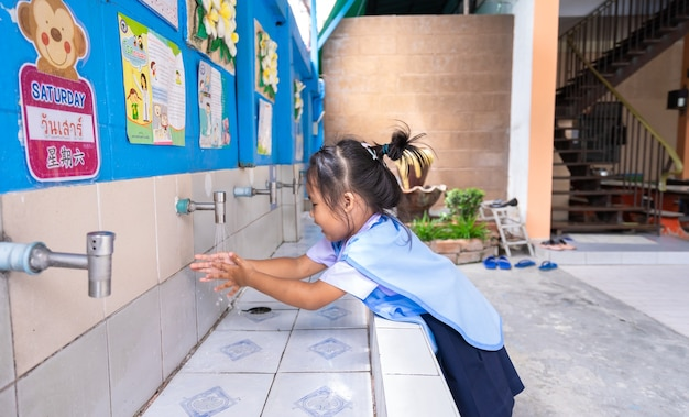 Little girl wash her hands before eating at school