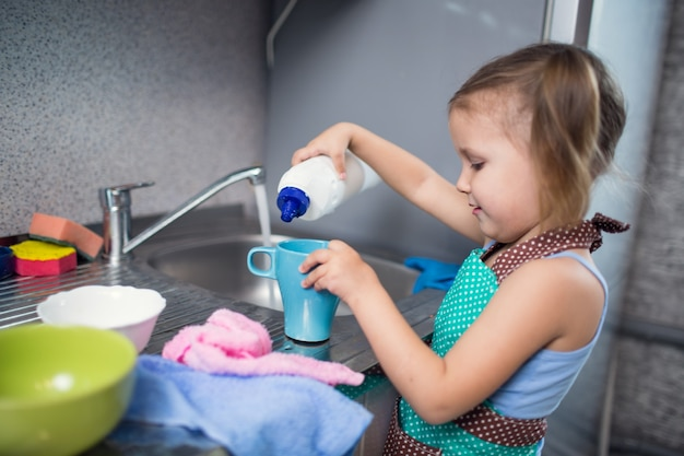 Маленькая девочка моет посуду дома на кухне в раковине