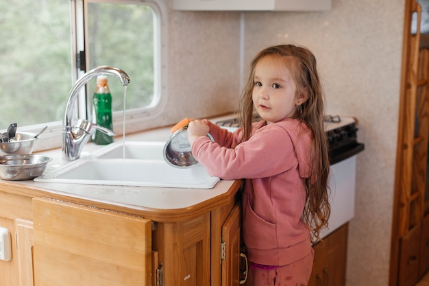 Маленькая девочка моет посуду на кухне туристического трейлера