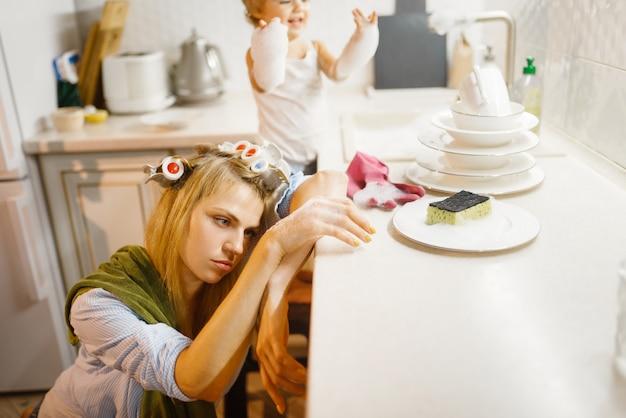 Маленькая девочка моет посуду возле усталой домохозяйки