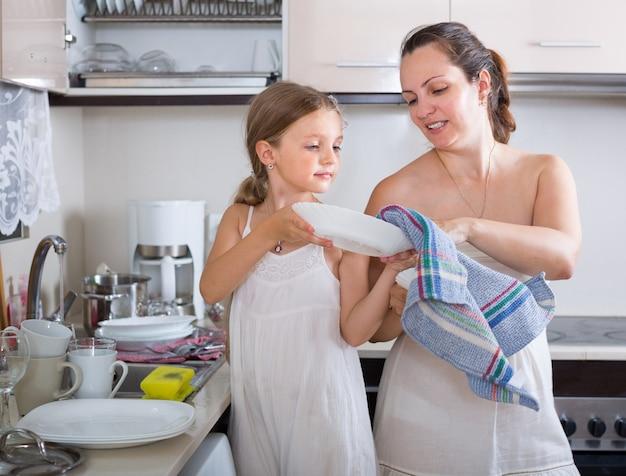 母親とプレートを洗う小さな女の子