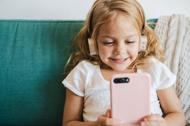 Маленькая девочка смотрит мультфильмы на своем телефоне